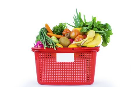 Organic vegetables and fruits in a plastic basket over the table in the studio. Isolated on white background