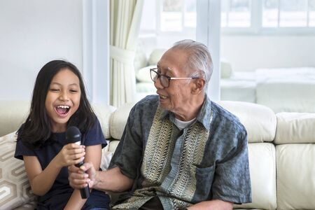 Happy little girl and her grandfather singing together with a microphone while sitting on the sofa in the living room at home