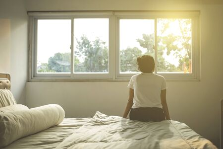 Back view of young woman sitting on the bed while enjoying sunset view in the apartment window