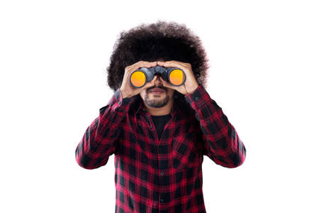 Young Afro man looking through a binocular while standing in the studio, isolated on white background