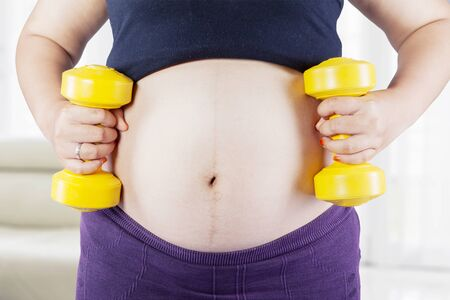 Close up of pregnant woman tummy doing workout with two dumbbells and standing in the living room at home