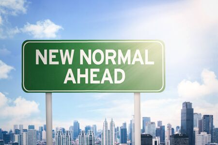 Signpost with New Normal Ahead text and modern city background