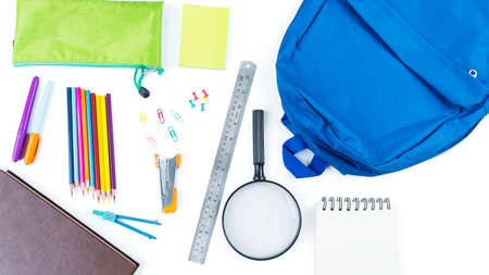 Top down view of blue backpack with surrounded by school supplies on the table. Isolated on white background