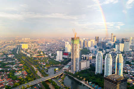 Aerial view of beautiful rainbow on the Jakarta skyline with quiet road and skyscrapers at morning time