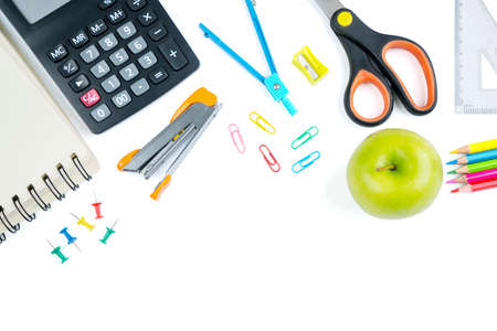 Top down view of green apple and school supplies on the table with copy space. Isolated on white background