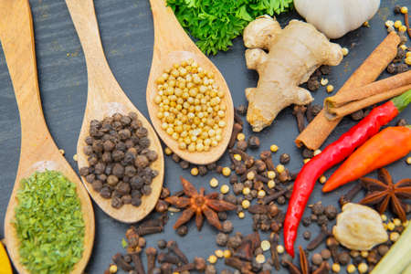 Close up of various herbs and spices in wooden spoons on the wooden table background