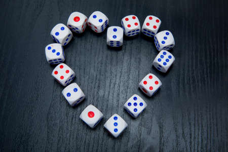Top view of gaming dice organized in heart symbol on the wooden table Stockfoto