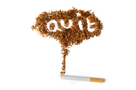 Quit smoking concept. Close up of a cigarette with quit smoking word made of dried tobacco on the table. Isolated on white background