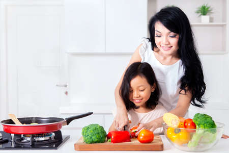 Happy mother and her daughter preparing to makes healthy salad while standing in kitchen room at home