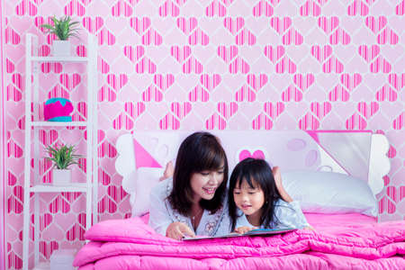 Happy mother and her daughter reading a book in bed before going to sleep. Shot at home