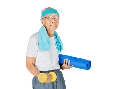 Senior man carrying a mat and dumbbell while preparing to yoga exercise in the studio. Isolated on white background