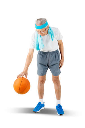 Elderly man wearing sportswear while dribbling a basketball in the studio. Isolated on white background