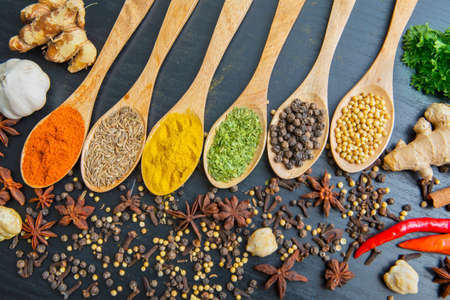 Top view of various herbs and spices on the wooden spoons for cooking on the wooden table