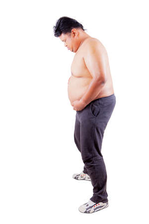 Full length of a young man holding his fat belly while standing in the studio, isolated on white background