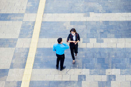 Top down view of two business people greeting with elbow while meeting and chatting on the sidewalk