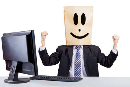 Young businessman with cardboard head celebrating success by lifting his hands while working with a computer in the studio with isolated on white background