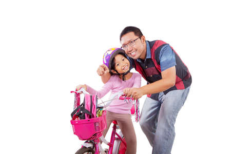 Happy father pointing at something while accompanying his cycled daughter in the studio. Isolated on white background