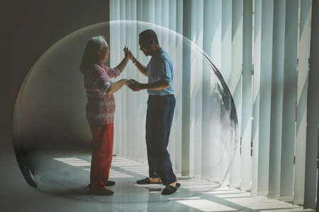 Elderly couple feels happy in protective bubble while dancing together near the window at home