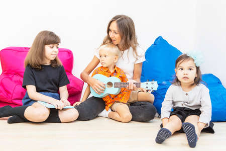 Happy teacher playing a guitar while singing with her pupils in the kindergarten