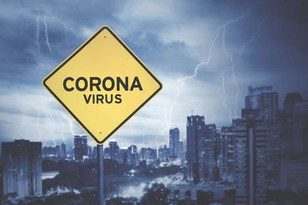 Yellow road sign with corona virus text on modern city background under cloudy sky