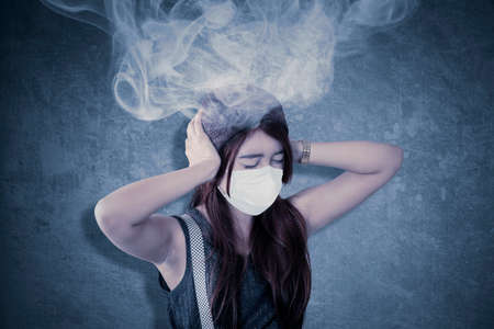 Angry teenage girl wearing face mask with smoke over head while getting bored during quarantine at the home