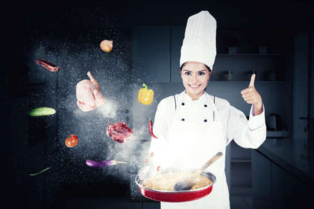 Female chef showing thumb up while cooking in the kitchen with flew food ingredients in a frying pan
