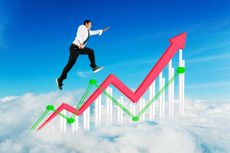 Asian businessman jumping with upward arrow and growth chart in the blue sky Stock Photo