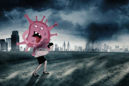 Young businesswoman carrying big coronavirus while walking on the road with storm city background