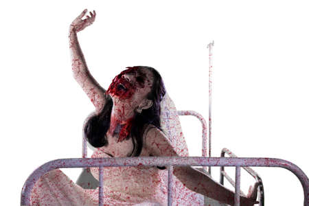 Halloween horror concept. Horrible female bride with wounded face sitting on the hospital bed, isolated on white background