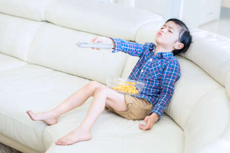 Picture of little boy looks bored while holding a television remote and sitting in the living room. Shot at home