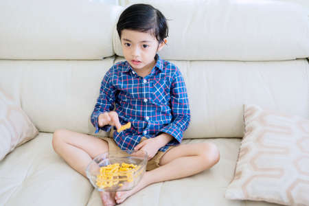 Adorable little boy changing channel television while eating a bowl of snack and relaxing on the couch. Shot at home Archivio Fotografico