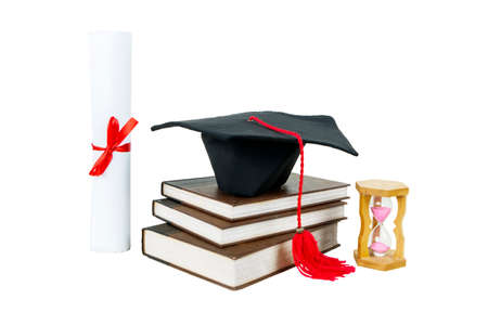 Close up of graduation cap on a pile of books with diploma and hourglass on the table, isolated on white background Standard-Bild