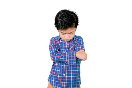 Picture of little boy crossed his arms while standing with sad expression in the studio. Isolated on white background