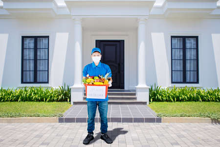 Delivery man wearing medical mask and standing in the front of customers house while holding a red basket full of fruits and vegetables with text of stay home we deliver 免版税图像