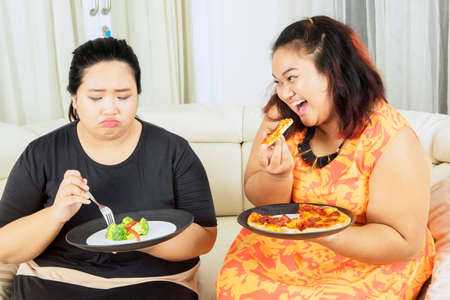Lose weight concept. Unhappy fat woman eating salad while teasing by her sister eating pizza with mocking expression 版權商用圖片