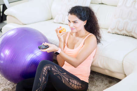 Indian woman eating an apple while watching television after exercising in the living room. Shot at home
