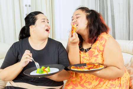 Lose weight concept. Young obesity woman eating pizza while teasing her fat sister eating salad in the living room. Shot at home 版權商用圖片