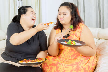 Lose weight concept. Happy fat woman eating pizza while teasing her overweight sister eating salad in the living room. Shot at home