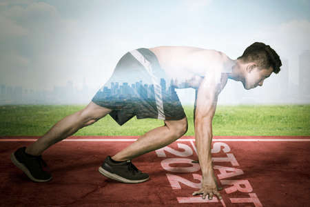 Double exposure of young man kneeling above start line and numbers 2021 while ready to run with modern city background
