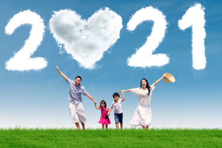 Happy family running on the meadow while holding hands together with clouds shaped number 2021 and heart symbol in the blue sky
