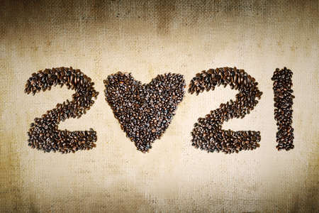 Top view of roasted coffee beans shaped 2021 numbers and heart symbol on the burlap sack background 版權商用圖片