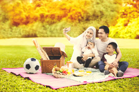 Muslim family using a cellphone to taking a selfie photo together while picnicking in the park with autumn trees background