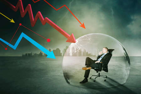 Confident businessman sitting on the chair in bubble to protect from attacks declining arrows with cloudy sky background Reklamní fotografie