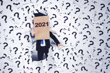 Disoriented businessman wearing cardboard with 2021 numbers on his head while walking with question marks symbol background Standard-Bild