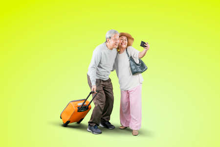 Happy old couple taking a selfie photo together by using a smartphone while carrying a luggage in the studio with green screen background