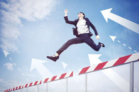 Low angle view of young businesswoman jumping through hurdles with upward arrows with blue sky background Banque d'images