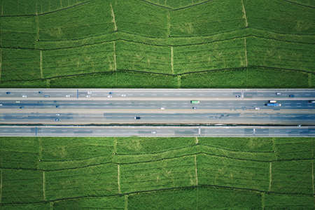 Top down view of cars passing through elevated road and tollway surrounded green rice fields in Jakarta city, Indonesia