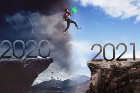 Female college student jumping through gap from number 2020 with cloudy sky to number 2021 with clear sky. Future better concept