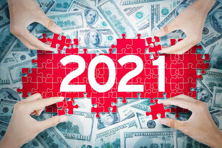 Top view of four people hand is composing puzzle with number 2021 on the heaped money background Foto de archivo