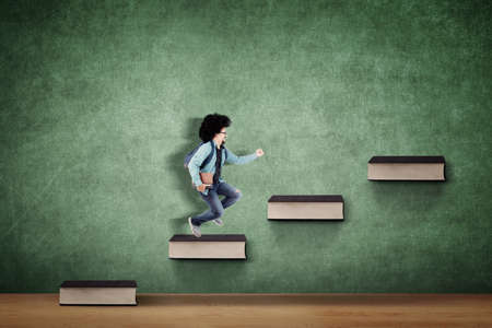 Afro male college student carrying book and bag while climbing stairs of book with chalkboard background Zdjęcie Seryjne